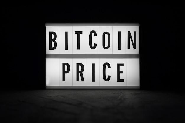 ビットコイン価格-暗闇の中で明るいディスプレイ上のテキスト。暗号通貨ニュース。