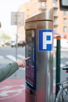 Парковка машины на городской улице. терминал для оплаты парковки. мужская рука нажимает кнопку.
