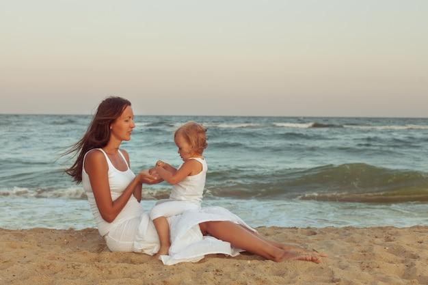 ママと娘は海の近くのビーチの砂の上に座っています。