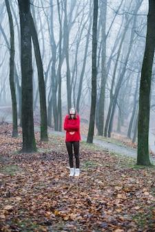 若い女の子は一人で霧の森で迷子になり、恐怖、憂鬱、孤独を感じる