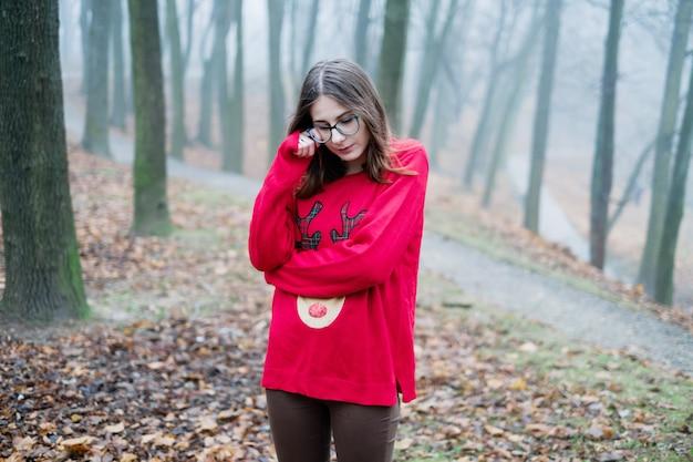 若い女の子は一人で霧の森で迷子になり、恐怖、憂鬱、孤独を感じて泣きます