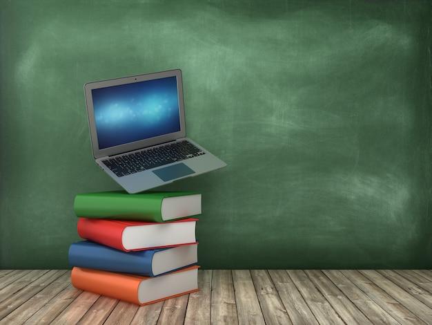 黒板上の本とコンピューターのラップトップ
