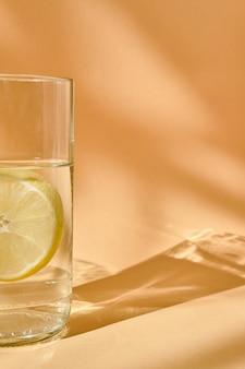 В кадре видна часть стакана воды с лимоном