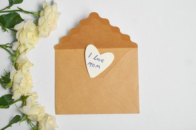 カードと白いバラのクラフト封筒。母の日のコンセプトです。