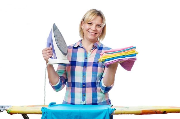 Красивая женщина домохозяйка гладит одежду