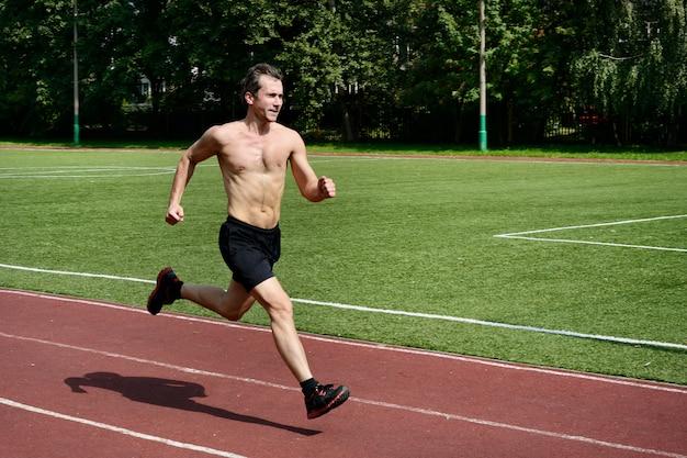 Спортсмен бегун тренируется на стадионе