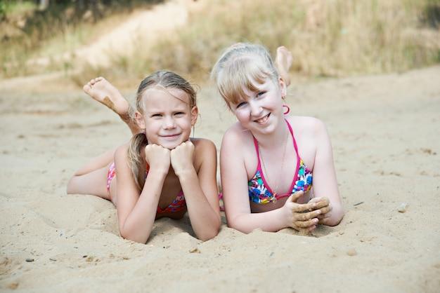 Счастливые маленькие девочки на песчаном пляже