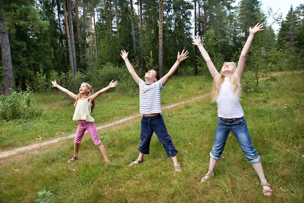 Дети на лужайке леса и наслаждаться жизнью в спорте