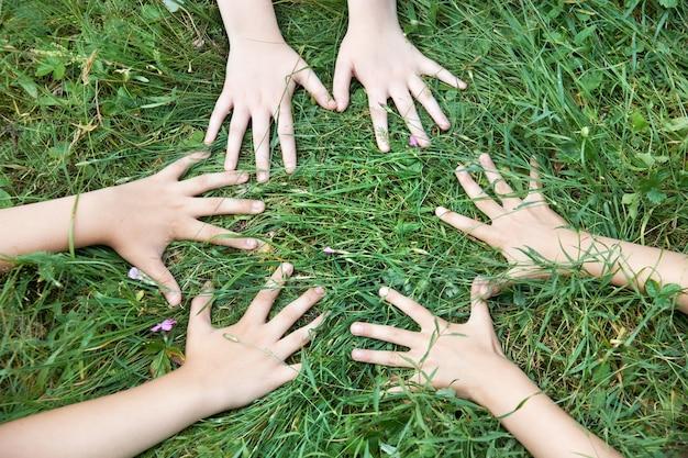 芝生の上で子供たちの手
