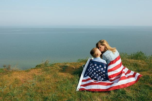 Мать-одиночка с сыном на день независимости сша. женщина и ее ребенок гуляют с флагом сша на берегу океана