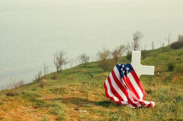 Могила солдата. американский флаг над могилой погибшего солдата. на могиле военная кепка
