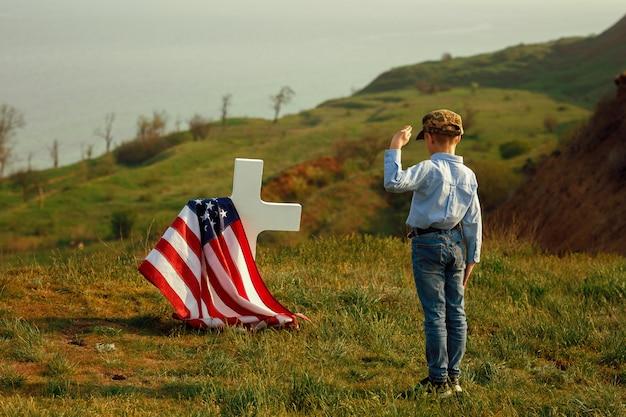 軍事帽子をかぶった少年が記念日に父の墓に敬礼