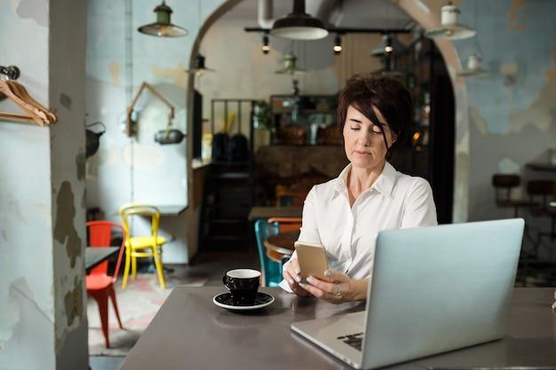 Женщина средних лет сидит в кафе, пьет кофе и работает за компьютером. женщина телефона удерживания