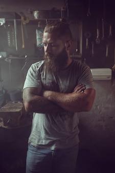 Красивый брутальный мужчина с бородой стоит в своем гараже на фоне инструментов ремонта