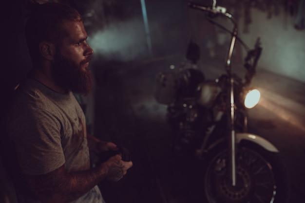 Красивый брутальный мужчина с бородой стоит в своем гараже на фоне мотоцикла и смотрит в сторону