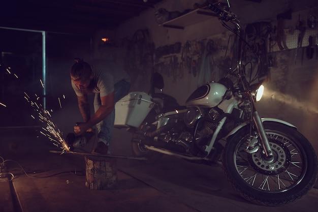 Красивый зверский мужчина с бородой ремонтируя мотоцикл в его гараже работая с круглой пилой. в гараже много искр и дыма от распиловки