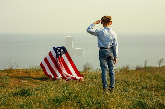 Молодой мальчик в военной фуражке приветствует могилу своего отца в день поминовения