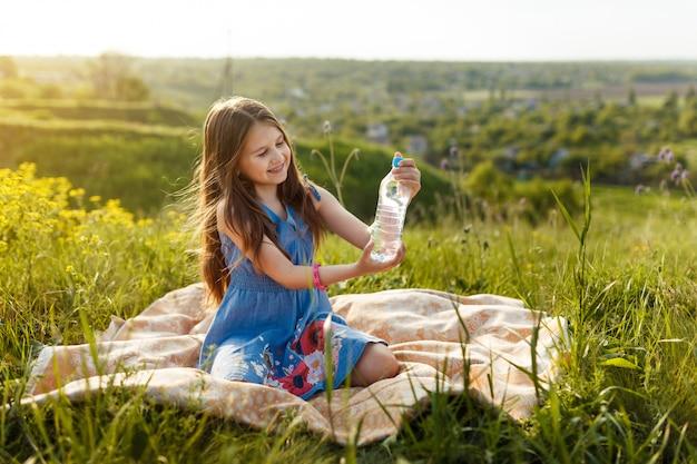 プラスチック製の水のボトルと草の少女