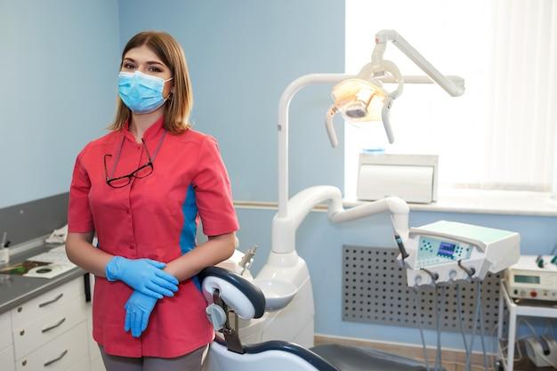 Девушка стоматолог стоит в середине их оборудования