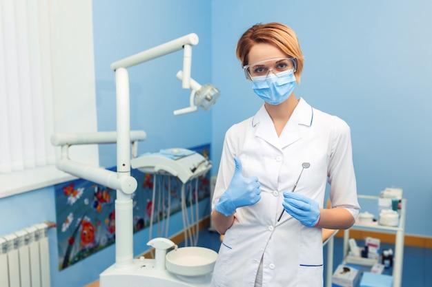 Стоматолог держит устройство для операции