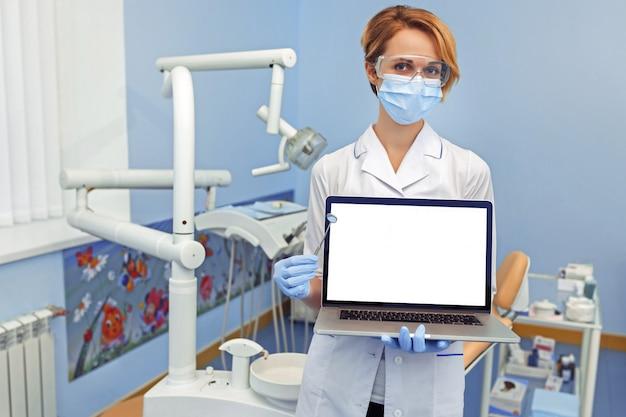 Стоматолог держит ноутбук с пустым местом для вашего изображения