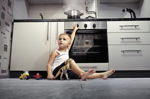 ガスストーブが付いている台所で遊ぶ子供。