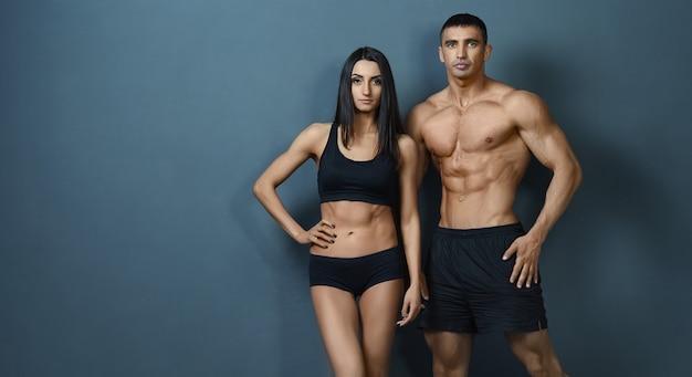 壁の背景にポーズスポーツ体と若いカップル
