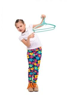 ハンガーでシャツを保持している笑顔の少女。切り取る