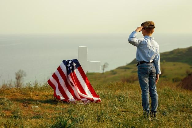 記念の日に軍の帽子をかぶった少年が父親の墓に敬礼する