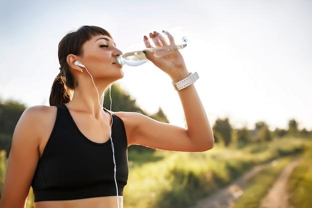 スポーティな若い女性は水を飲む