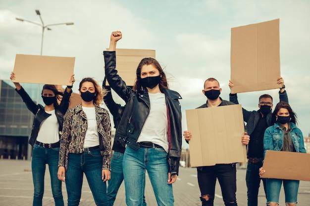 Группа людей с маской и плакатами в знак протеста протест населения против коронавируса
