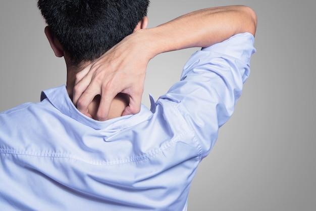 Молодой человек руки чесать по спине с рубашкой