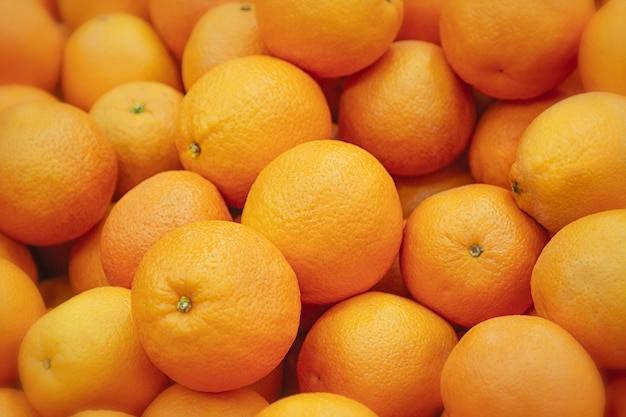 新鮮なみかんのテクスチャです。カウンターの上に横たわる新鮮なオレンジ-ラウンドオレンジとみかんのオレンジとみかんのテクスチャ