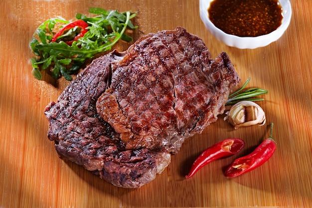 Сочный вкусный жареный мясной стейк на деревянной разделочной доске с перцем, чесноком, зеленью и томатным соусом. стейк для ресторана на деревянном фоне