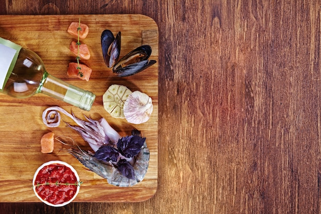 カットボードと木製テーブル、シーフードセット-ムール貝、エビ、タコ、バジル、サーモンとハーブの小片に白ワインと赤ソースのボトル