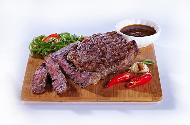 ジューシーで美味しいミディアムフライドミートステーキを木製のまな板にコショウ、ニンニク、ハーブ、トマトソースで。白い背景の上のレストランのステーキ