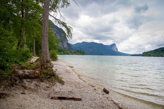 夏の終わりにバックグラウンドで山とアッターゼーの湖畔の穏やかな曇りの日。オーストリアのザルツカンマーグートのアッター湖