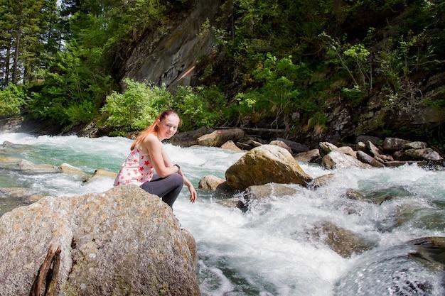 川の近くの石の上に座っている若い女性