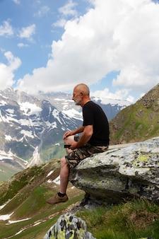 山の頂上の男。老人は山の上に座っています。退職後のアクティブな休暇。