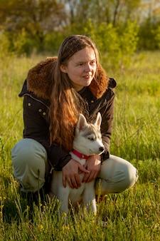 Девушка в парке своего дома с щенком хаски