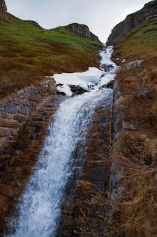 Каскад падает на моховые скалы