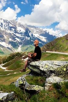 Пожилой мужчина на вершине горы