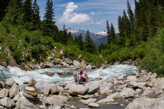 Девушка играет с хаски на берегу горной реки