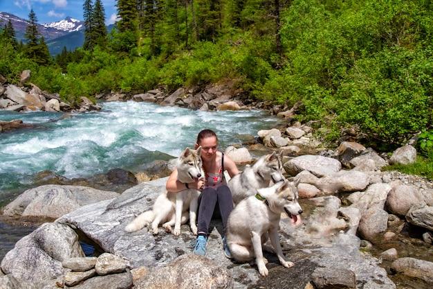 Девушка играет с собаками хаски на берегу горной реки