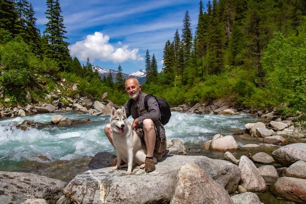 Мужчина сидит возле реки со своей собакой