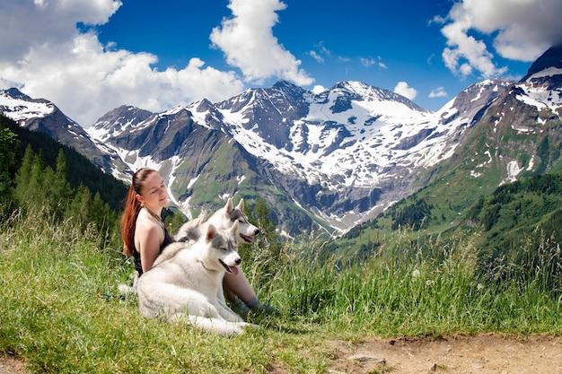 Девушка играет с хаски в горах