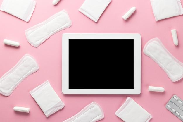 Тампоны, женские гигиенические прокладки и гаджет на розовом фоне. гигиеническая помощь в критические дни.
