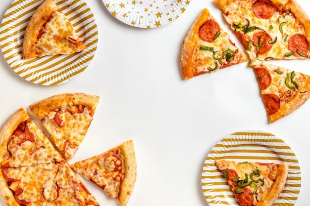 白い背景のペパロニとチーズのおいしい新鮮なピザのスライスジャンクフードの誕生日。テキストのコピースペースを持つ平面図です。フラットレイ