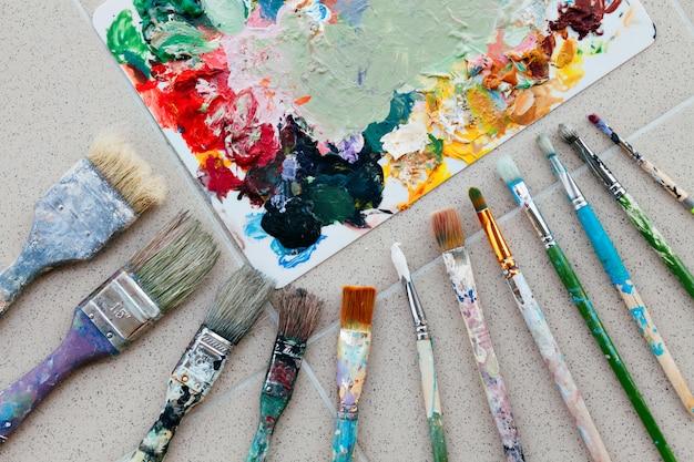 Кисти с палитрой в творческой композиции. красочный элемент