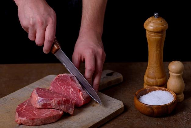 男はまな板で牛肉を切る